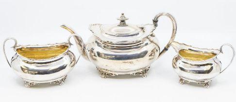 A George V silver three piece teaservice, cut card rims above plain bulbous bodies on scroll feet,