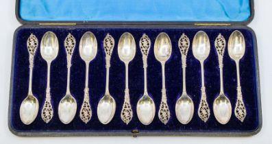 A set of twelve Victorian silver teaspoons, ornate openwork handles, hallmarked by William Comyns,