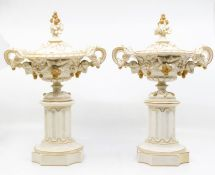 A pair of Royal Worcester lidded urns, on pillars, with fruit and leaf design