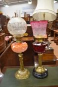 Two Victorian brass and glass oil lamps with shades and funnels