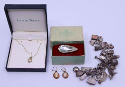 A white metal chain bracelet with numerous charms, total weight 115.7g, together with pair of 9ct