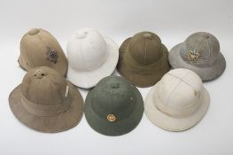 Set of seven colonial helmets ENGLAND AND USA Five Wolseley-type helmets. One is slimmer, bearing