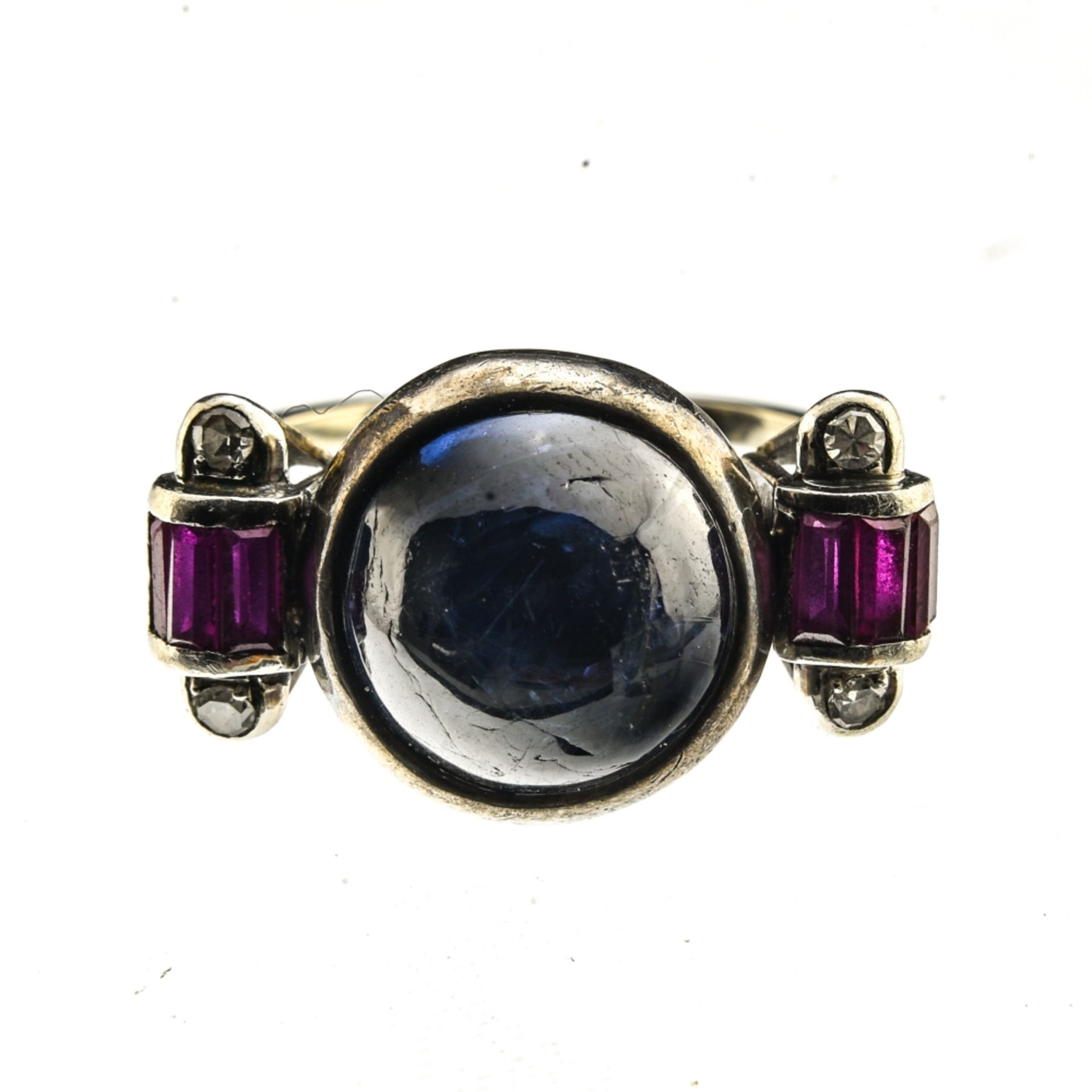 Art Deco ring 14 kt grey gold, set with a synthetic (Verneuil) sapphire cabochon, flanked by two