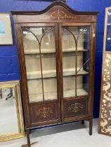 Edwardian mahogany inlaid glazed bookcase on slender supports. 66ins. x 34ins. x 11ins.