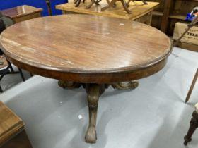 Late 19th cent. Mahogany oval tilt top loo table on ornate heavy three legged base with castors (