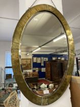 Early 20th cent. Oval beaten brass bevel edged mirror in the Arts and Crafts style. 31ins.