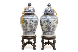 A PAIR OF LARGE BLUE & WHITE JARS AND COVERS ON STAND