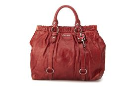 A MIU MIU PLUM RED LEATHER HANDBAG