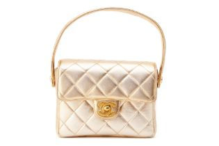 A CHANEL SMALL GOLD QUILTED FLAP BAG WITH TOP HANDLE