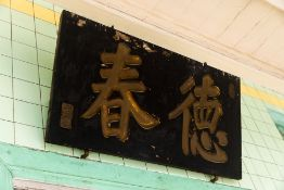 A BLACK AND GILT CHINESE SIGN