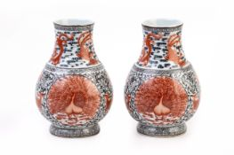 A PAIR OF IRON RED AND BLACK PEACOCK VASES