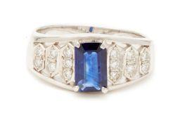 AN EMERALD CUT SAPPHIRE AND DIAMOND RING
