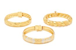 A GROUP OF THREE GOLD BANGLES