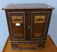 An oak table top shop cabinet, bearing Sunlight Soap inscription to doors
