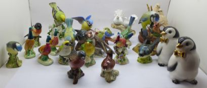 A collection of twenty bird figures including Beswick and a novelty penguin salt and pepper pair, (