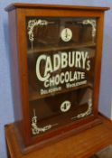 A mahogany counter top shop display cabinet, bearing Cadbury's Chocolate inscription to door,