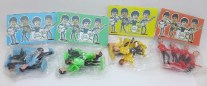 The Beatles; four sets of Beatles cake toppers in packets