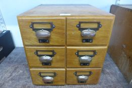 An oak table top six drawer index filing cabinet