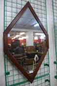 An oak framed diamond shaped mirror