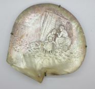 A large oyster shell, the mother of pearl with carved scene of a fisherwoman mending the nets with