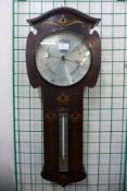 An Arts and Crafts inlaid rosewood aneroid barometer