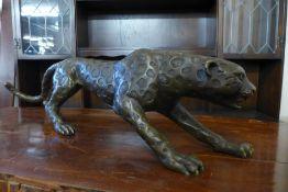 A bronze figure of a crouching leopard, 21cms h x 79cms l