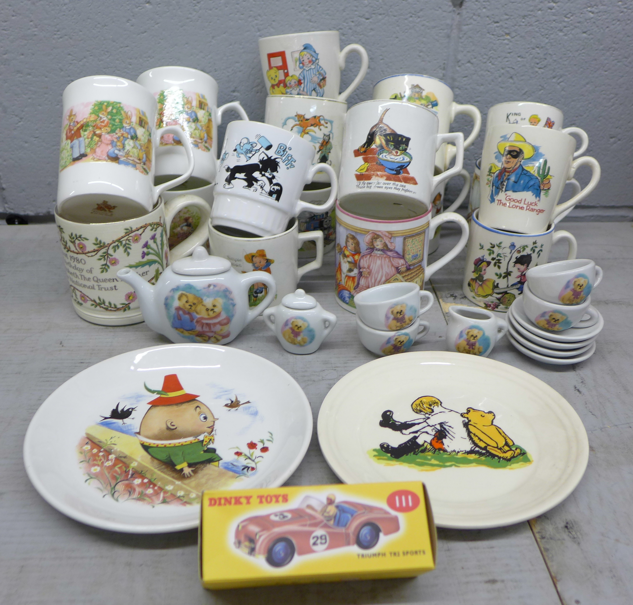 An assortment of childrens mugs, plates, a toy tea set and a Boncath pottery Queen Elizabeth 80th