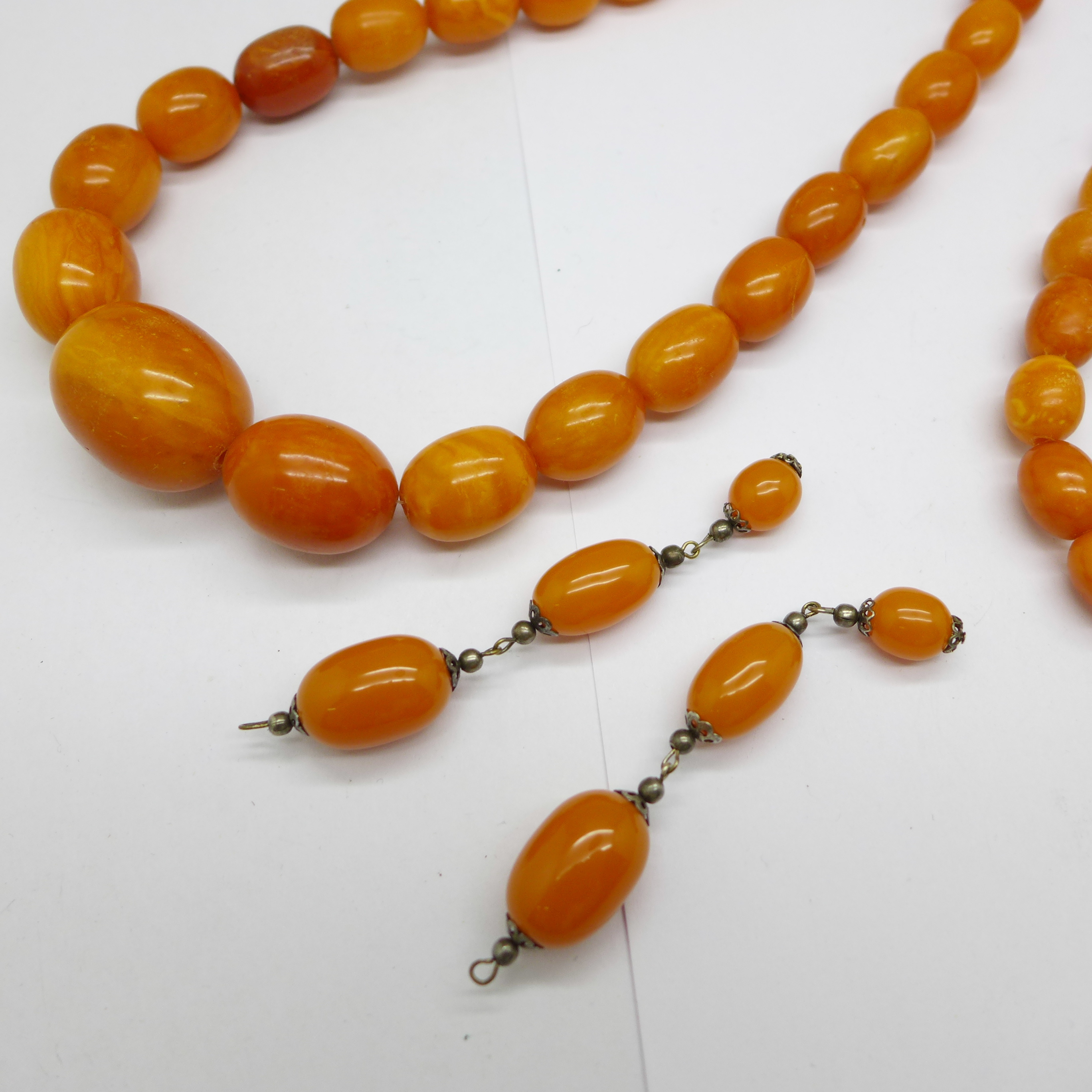 A large amber necklace, 94g, largest bead 29mm, 80cm, and a pair of drop earrings lacking hooks - Image 2 of 2