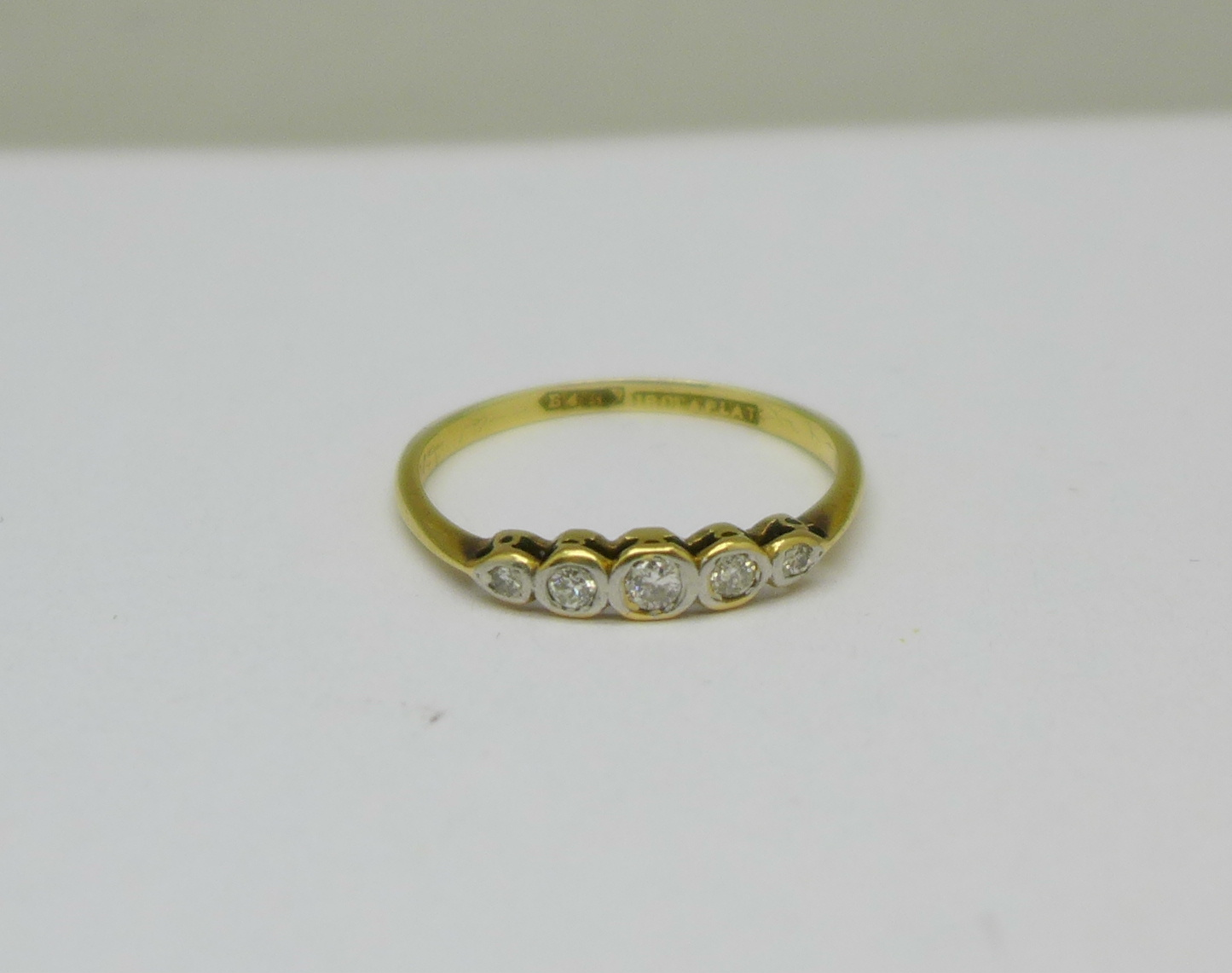 An 18ct gold, platinum set five stone diamond ring, 1.7g, O
