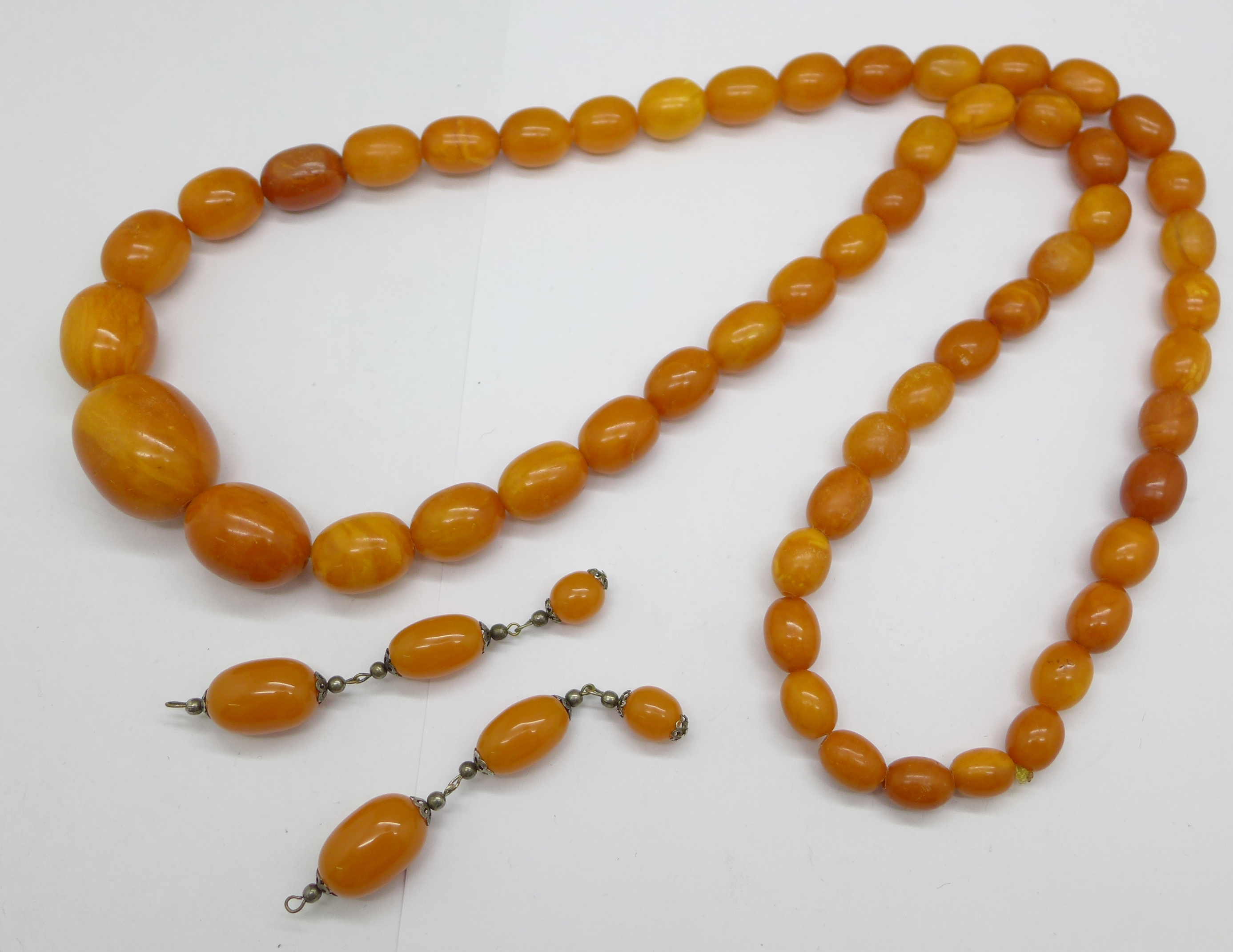 A large amber necklace, 94g, largest bead 29mm, 80cm, and a pair of drop earrings lacking hooks