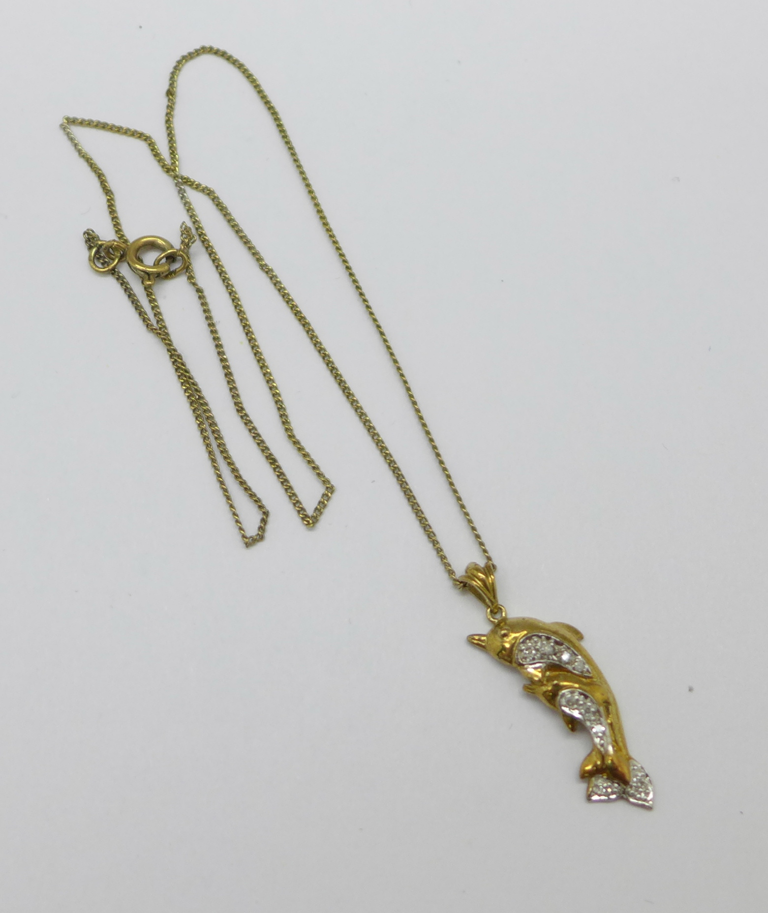 A 9ct gold dolphin pendant on chain, set with nine diamonds, pendant 25mm