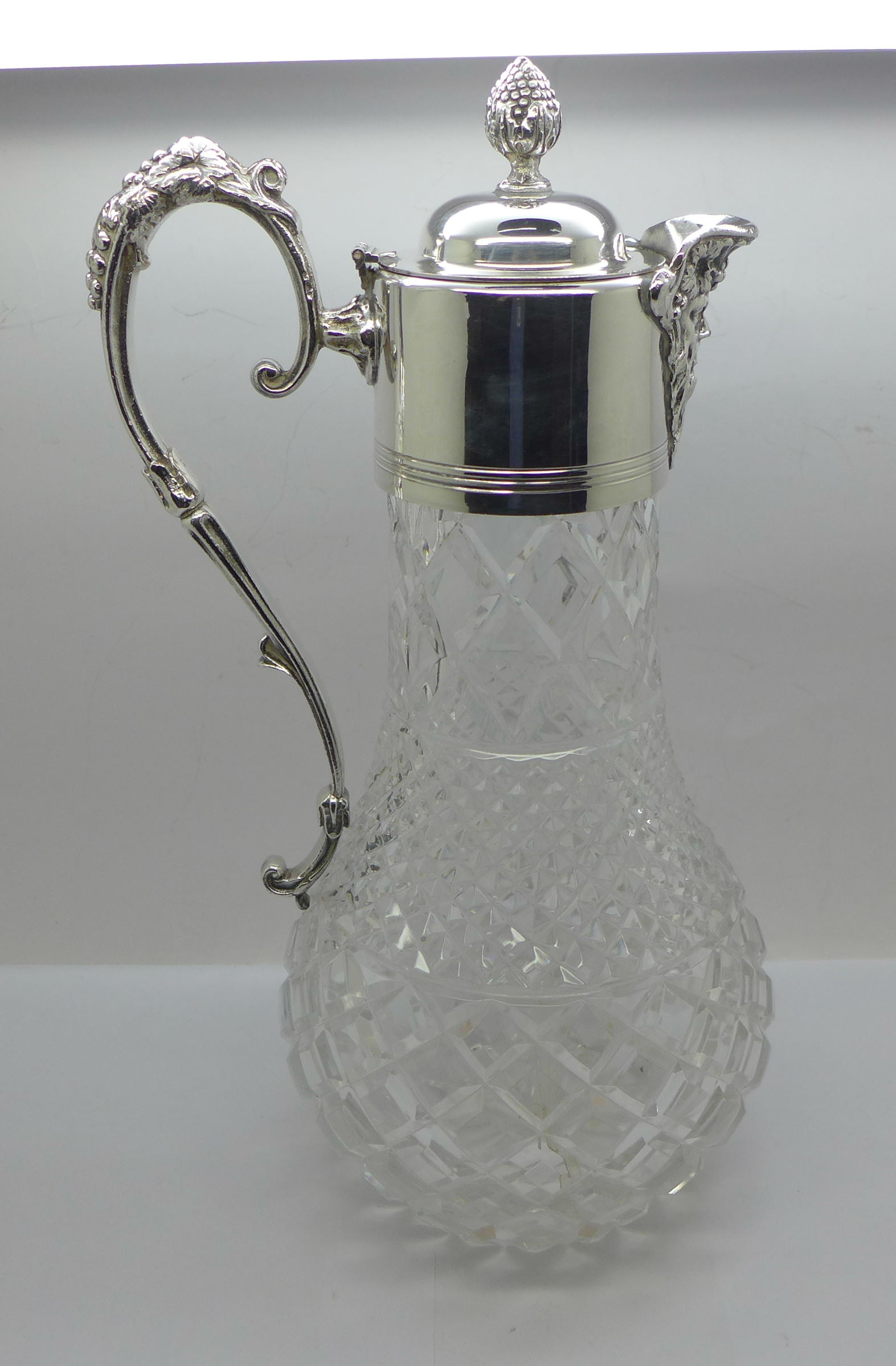 A white metal mounted glass claret jug, marked 999 on the handle and lid
