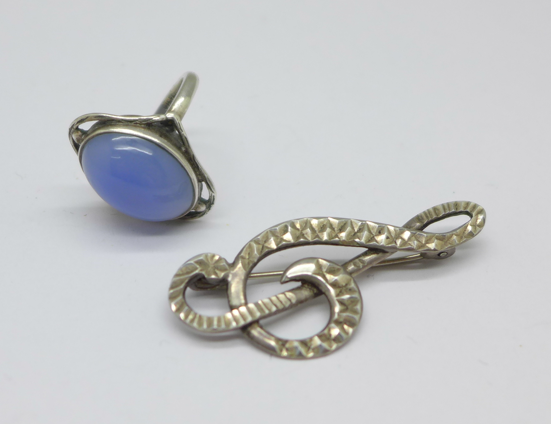 An Arts & Crafts silver ring set with chalcedony, L, and a treble clef brooch marked silver