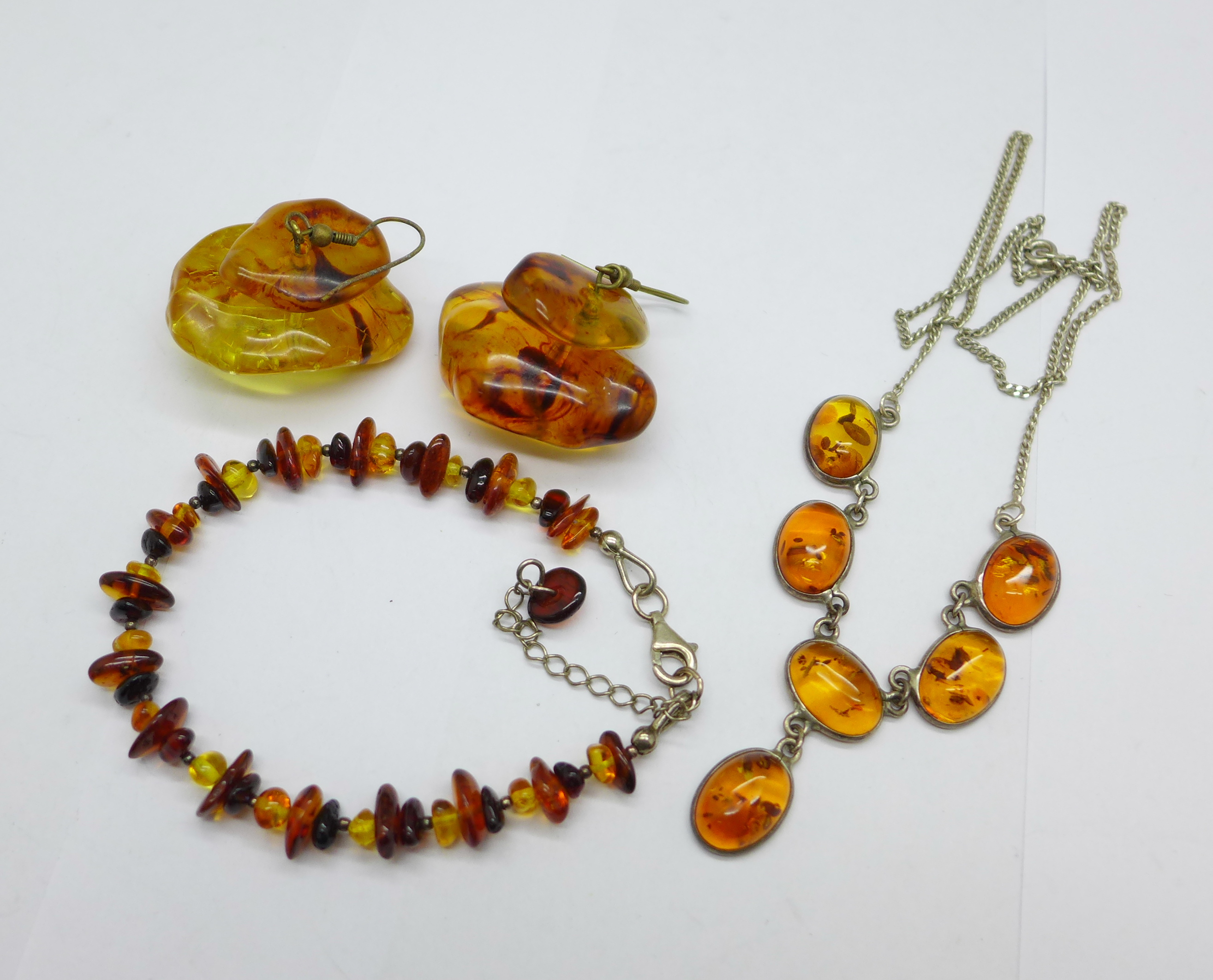 Amber coloured jewellery comprising a bracelet, earrings and a necklace
