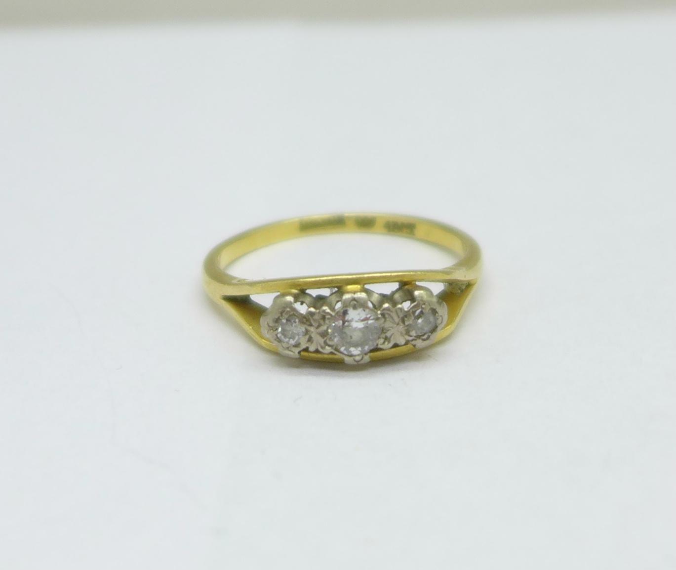 An 18ct gold and three stone diamond ring, 3.9g, Q