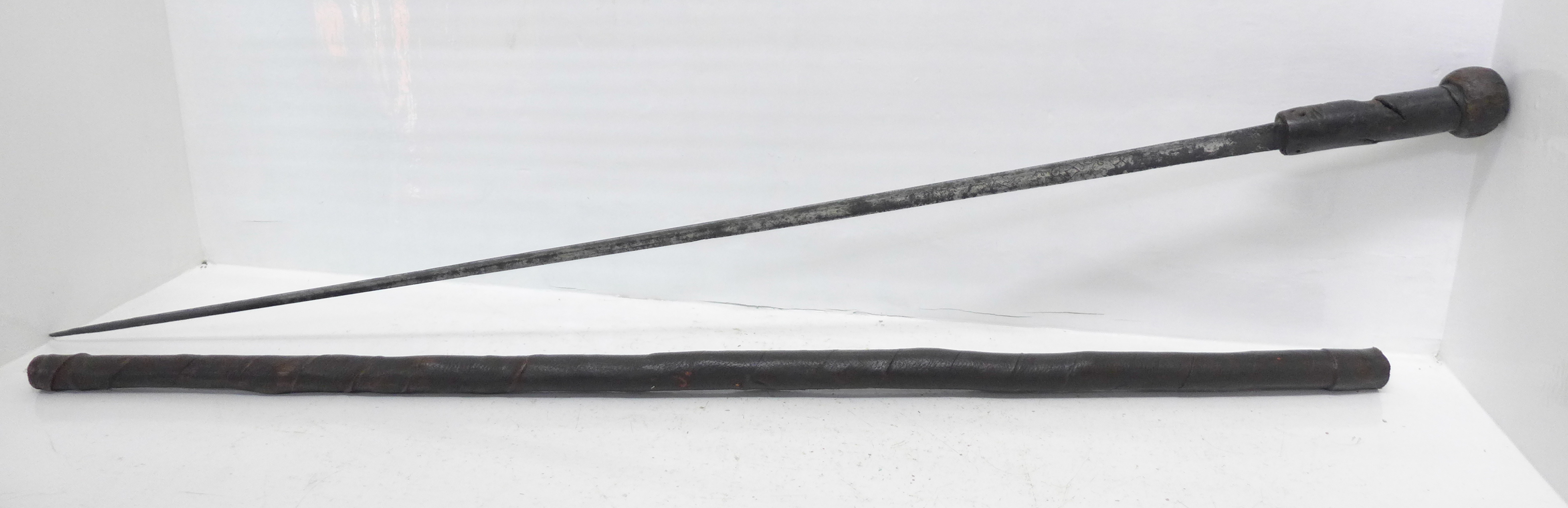 An early 19th Century swordstick, with decorated blade and leather scabbard, circa 1820