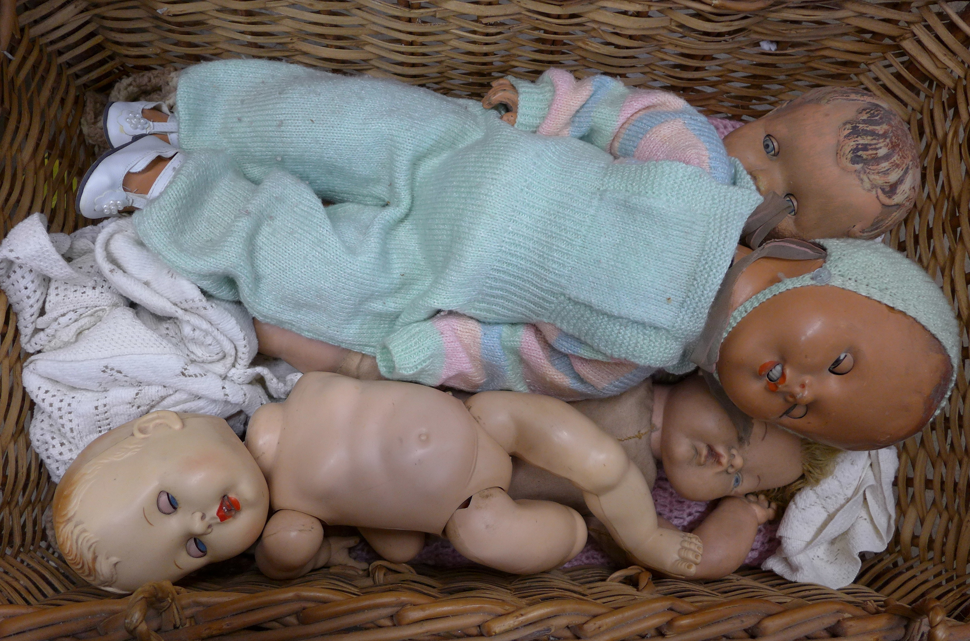 A wicker basket containing dolls **PLEASE NOTE THIS LOT IS NOT ELIGIBLE FOR POSTING AND PACKING**