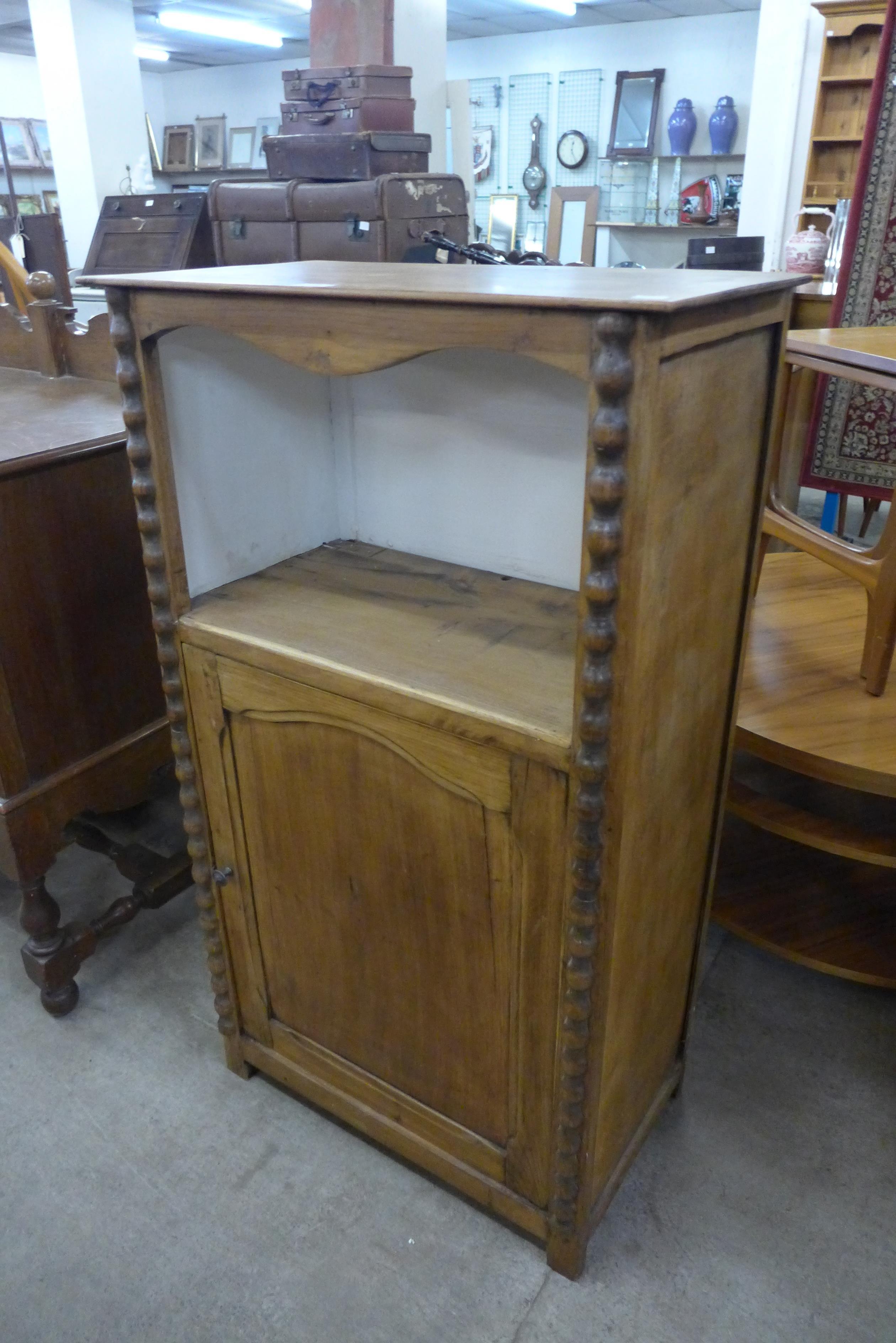 A 19th century French fruitwood bobbin single door cupboard