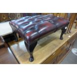A red leather buttoned footstool