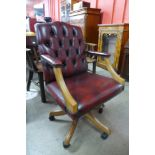 A beech and red leather revolving desk chair