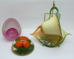 A Franz Porcelain cup and saucer with display stand, a French glass paperweight and one other