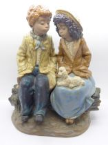Nao by Lladro, a large figurine of a boy and girl sitting on a log, E-2S backstamp, 25.5cm