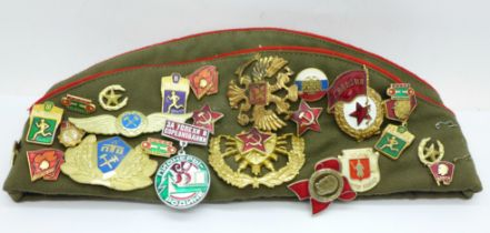 A Russian Army cap with 27 cloth and enamel badges