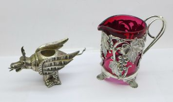 A cranberry glass jug in a plated mount and a plated model of a dragon