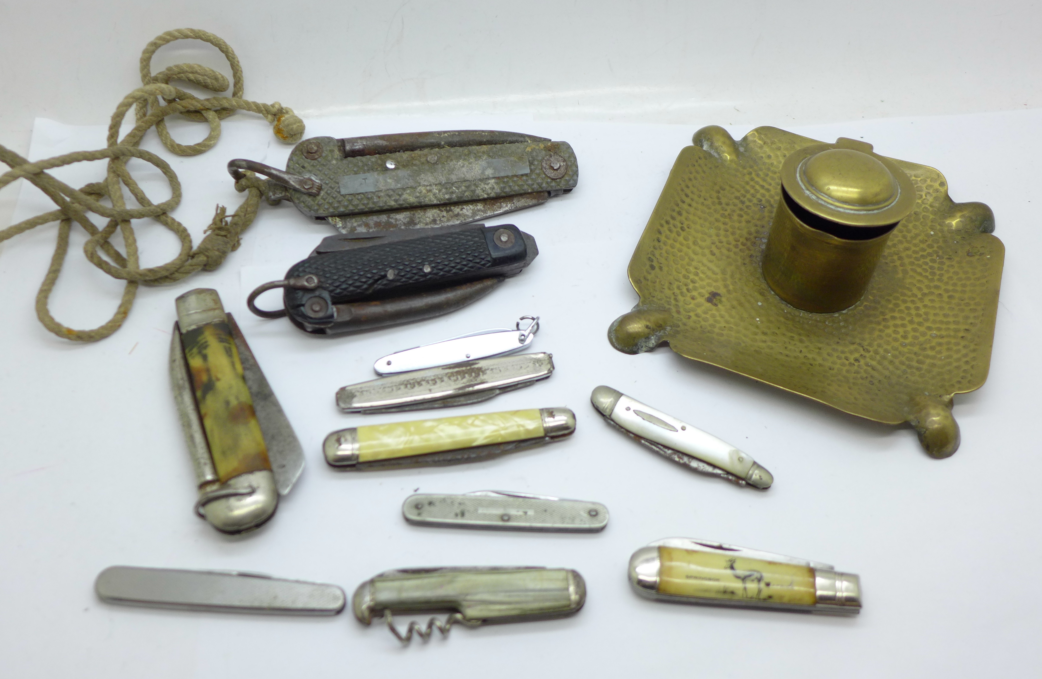 A brass inkwell and a collection of Army and other pocket knives