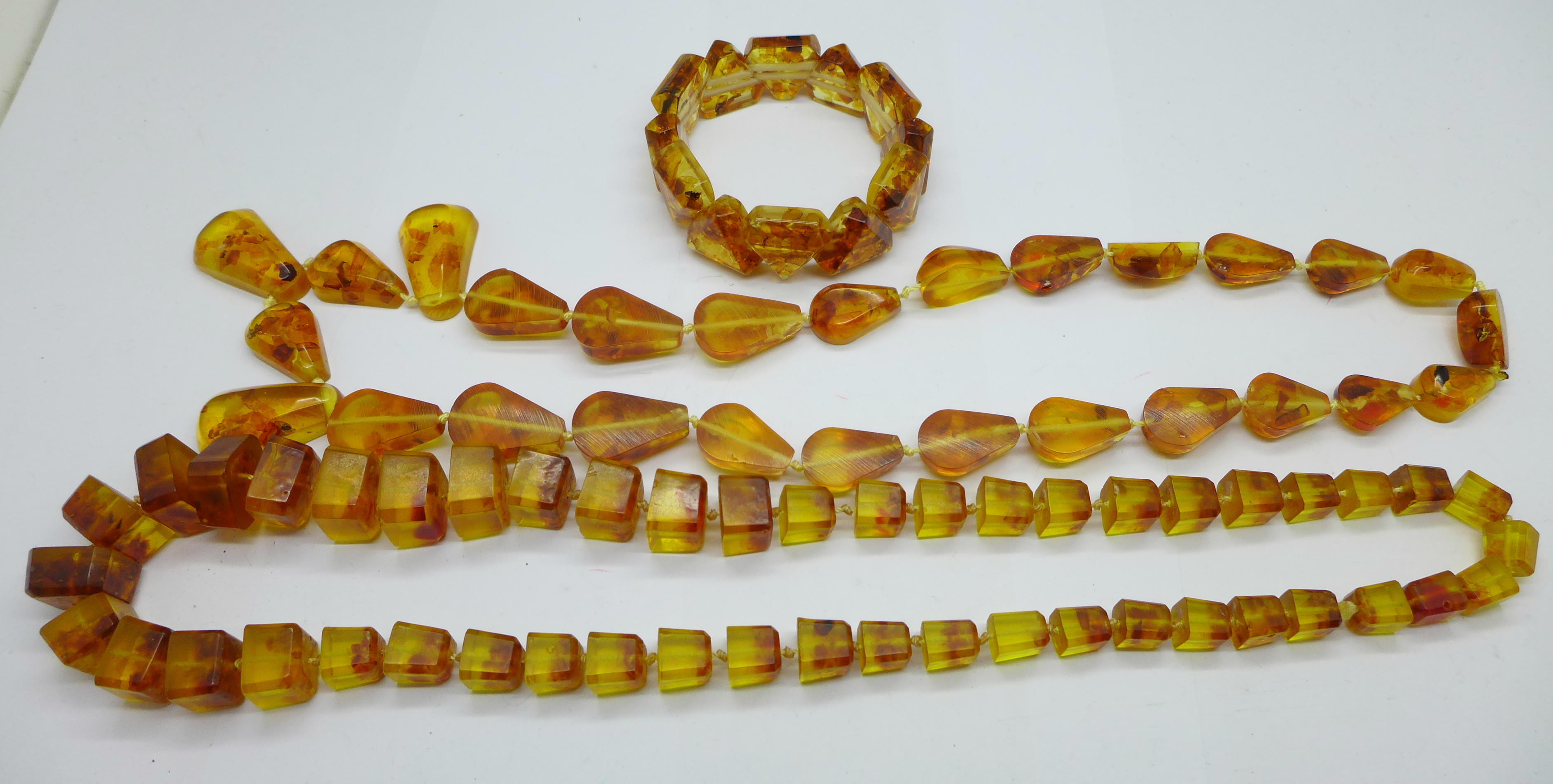 Two amber coloured bead necklaces and a bracelet