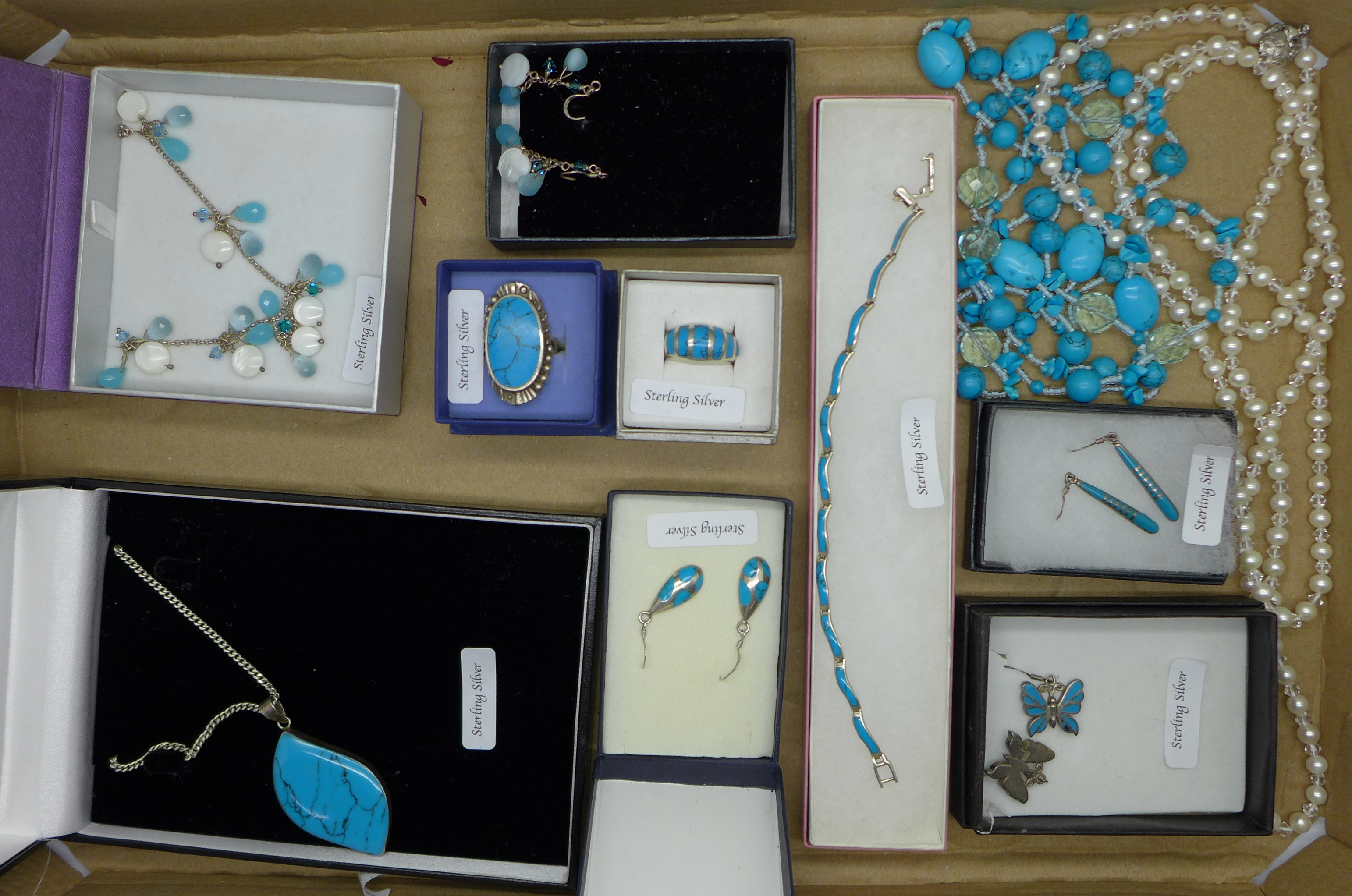 A collection of turquoise set silver jewellery