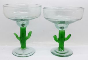 Two similar glass pedestal dishes, with green glass cactus stems and with pontil marks