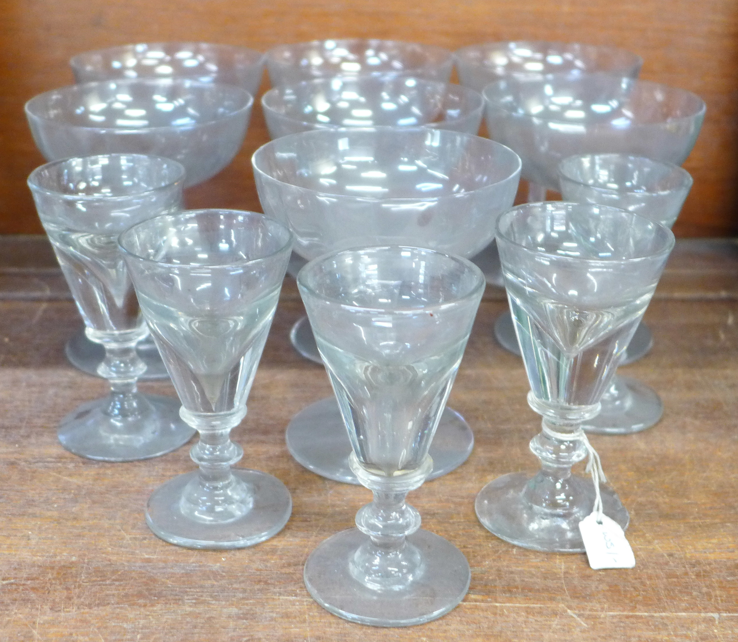 Seven 19th Century champagne coupes and five penny licks