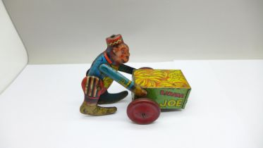 A vintage tin-plate clockwork toy monkey on a cart, marked made in England
